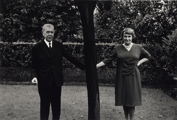 Rene and Georgette Magritte holding hands behind a tree - 1965